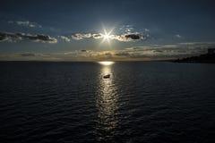 在光柱捉住的划艇降低的太阳的 在海,艾塞克斯的绍森德 免版税库存图片