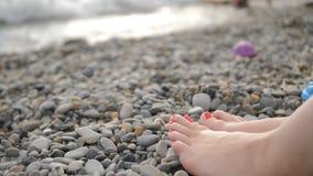 在光滑的小卵石的妇女的脚在一个pebbled海滩 影视素材