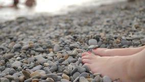 在光滑的小卵石的妇女的脚在一个pebbled海滩 股票录像