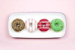 在光玫瑰色背景隔绝的盘子的四个五颜六色的油炸圈饼 免版税库存图片