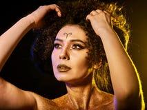 在光秃的妇女的金黄粉末化妆用品担负与装饰 库存照片