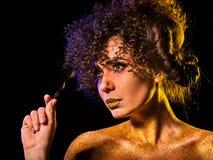 在光秃的妇女的金黄粉末化妆用品担负与装饰 图库摄影