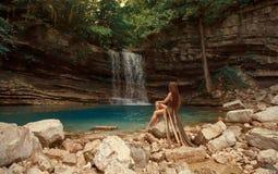 在光秃的岩石的神奇河若虫在小蓝色湖在马尔特维利峡谷盐水湖和美妙的瀑布,女孩附近与 免版税库存照片