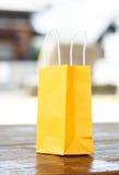 在光被弄脏的背景的一个黄色袋子 库存图片