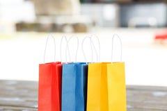 在光被弄脏的背景的五颜六色的纸袋 免版税库存照片