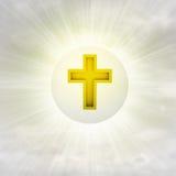 在光滑的泡影的基督徒金黄十字架在与火光的天空中 图库摄影
