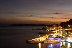 在克罗地亚手段Podgora,太阳和五颜六色的城市照明前条射线的日落  库存照片