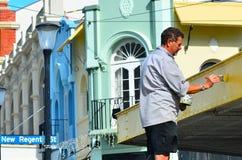 在克赖斯特切奇供以人员油漆在新的摄政的街道的损坏的大厦 免版税库存图片