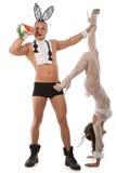 在兔子服装的可爱的夫妇用红萝卜 免版税库存图片