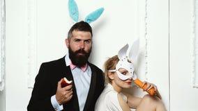 在兔子服装的夫妇用红萝卜和苹果 在白色背景的性感的兔宝宝夫妇 画报妇女,葡萄酒,神色 股票录像