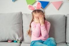 在兔宝宝耳朵哭泣的翻倒的小的逗人喜爱的女孩在家复活节庆祝概念 库存图片