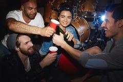 在党的凉快的青年人饮用的啤酒在夜总会 库存照片