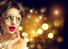 在党的秀丽式样妇女佩带的威尼斯式化妆舞会狂欢节面具 免版税库存图片