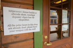 在入口的信息标志对指示的纪念品店不输入与武器在朗伊尔城,挪威 免版税库存图片
