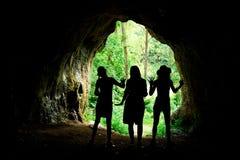 在入口的女性剪影对在forrest的自然洞 免版税图库摄影