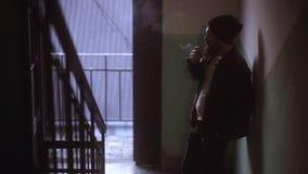 在入口的英俊的年轻人抽烟的香烟 有雪茄和烟的奥秘人 股票视频
