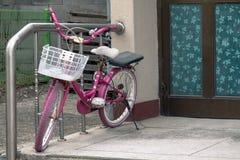 在入口附近的停放的儿童的自行车对房子 图库摄影
