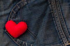 在全力以赴红色老蓝色牛仔裤 对牛仔布的手段爱 免版税图库摄影