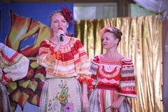 在全国俄国服装的阶段美丽的女孩,与充满活力的刺绣-伙计音乐小组的褂子sundresses轮子 免版税库存图片