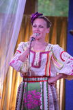 在全国俄国服装的阶段美丽的女孩,与充满活力的刺绣-伙计音乐小组的褂子sundresses轮子 图库摄影