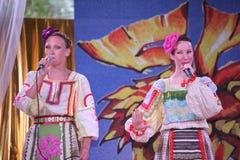 在全国俄国服装的阶段美丽的女孩,与充满活力的刺绣-伙计音乐小组的褂子sundresses轮子 免版税库存照片