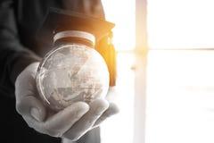 在全球性,在拿着地球的商人的毕业盖帽的教育 免版税库存图片