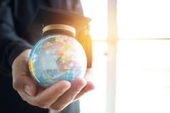 在全球性,在拿着地球的商人的毕业盖帽的教育 库存照片