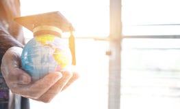 在全球性,在拿着地球的商人的毕业盖帽的教育 免版税图库摄影