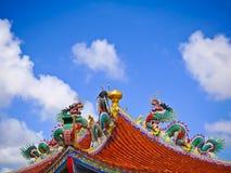 在八角形物亭子和蓝天屋顶的绿色瓷龙雕象  免版税库存图片