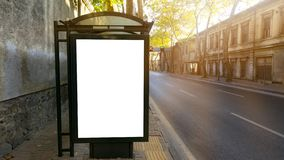 在公交车站的垂直的空白的白色广告牌在城市老街道上 在背景大厦和路 库存图片