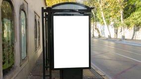 在公交车站的垂直的空白的白色广告牌在城市老街道上 免版税库存照片