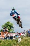 在公众前的高跳跃的摩托车车手 免版税库存图片