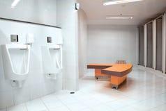 在公共厕所的白色瓷尿壶人的 免版税库存图片