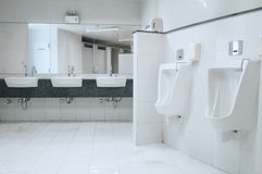 在公共厕所的白色瓷尿壶人的 免版税库存照片