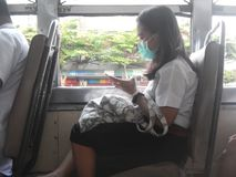 在公共汽车的女孩佩带的面具 Pm2 5尘土空气污染 r 免版税图库摄影
