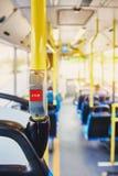 在公共汽车的红色按钮中止 有黄色扶手栏杆和蓝色位子的公共汽车 与太阳作用的照片,在透镜的强光从光 免版税库存照片