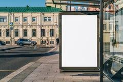 在公共汽车站的垂直的空白的广告牌在城市街道上 在背景大厦,路 嘲笑 在车行道旁边的海报 库存照片