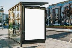 在公共汽车站的垂直的空白的广告牌在城市街道上 在背景大厦,路 嘲笑 在车行道旁边的海报 库存图片