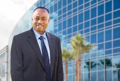 在公司大厦前面的英俊的非裔美国人的商人 库存图片