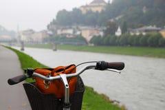 在公园、河和山的看法的一辆自行车 免版税库存照片