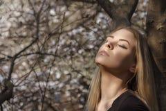 在公园享受温暖的阳光的一个女孩 免版税库存照片