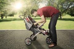 在公园供以人员和他的有婴儿推车的婴孩 库存照片