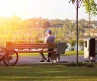 在公园供以人员有在长凳的一个咖啡休息,美丽如画的看法,日落 库存图片