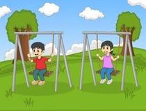 在公园动画片的儿童游戏摇摆 免版税库存照片