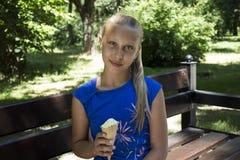 在公园吃冰淇凌的美丽的十几岁的女孩 免版税图库摄影
