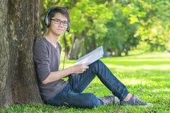 在公园听到在耳机的音乐的年轻学生 免版税库存图片