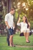 在公园女孩的夫妇摇摆的 图库摄影