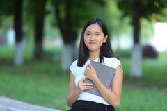 在公园学会与片剂的女孩 免版税图库摄影