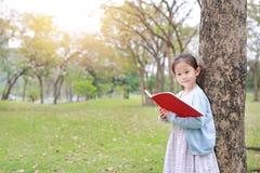 在公园室外站立的俏丽的小孩女孩看书精瘦反对树干在夏天庭院里 图库摄影
