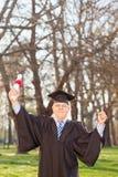 在公园成熟打手势幸福的毕业生 免版税库存照片